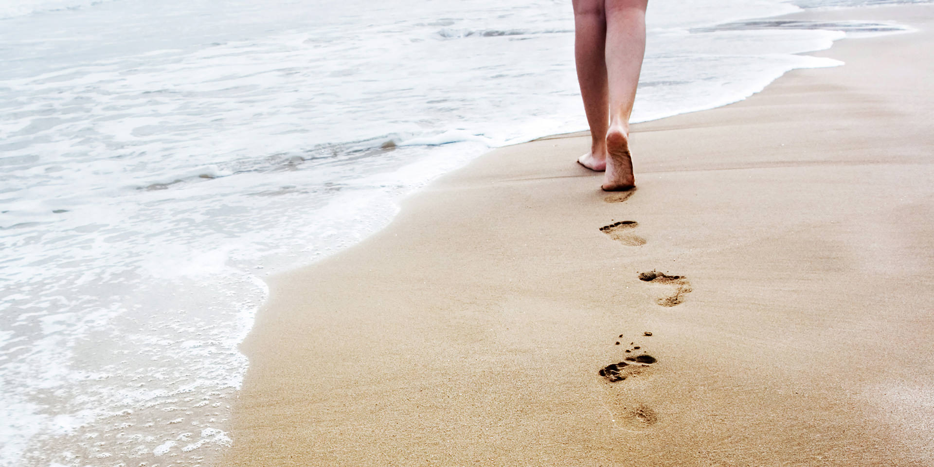 Barfuß am Meer im Sand laufen